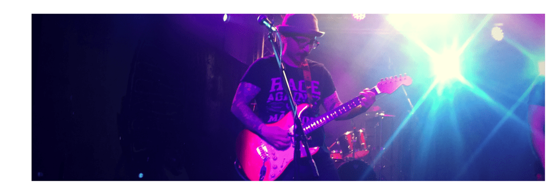 Sal Guzzo plays electric guitar on stage at a BIST 3rd party fundraiier in 2016
