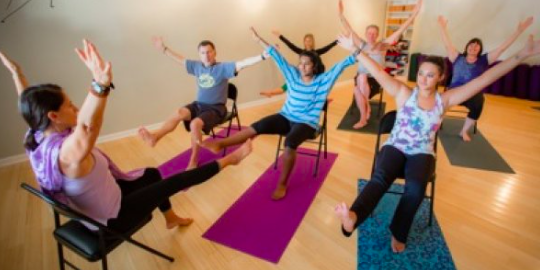 adults practising chair yoga