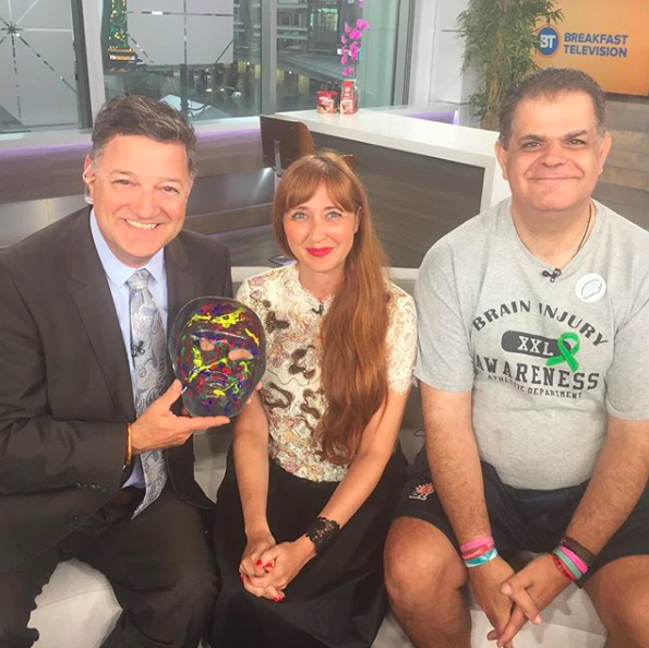 Kevin Frankish holds Frank's mask 'What's Wrong Look Inside' with Melissa Vigar and Frank Bruno